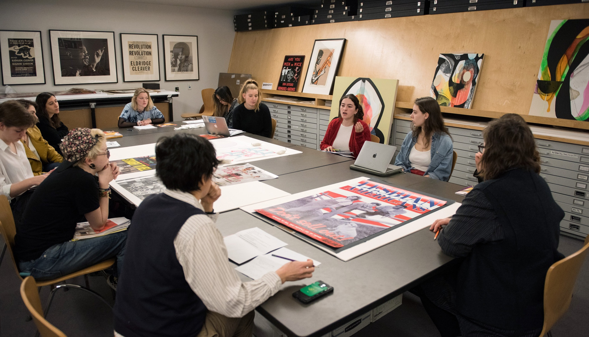 A group of young, light-skinned people sit around a table with posters laid out on it.
