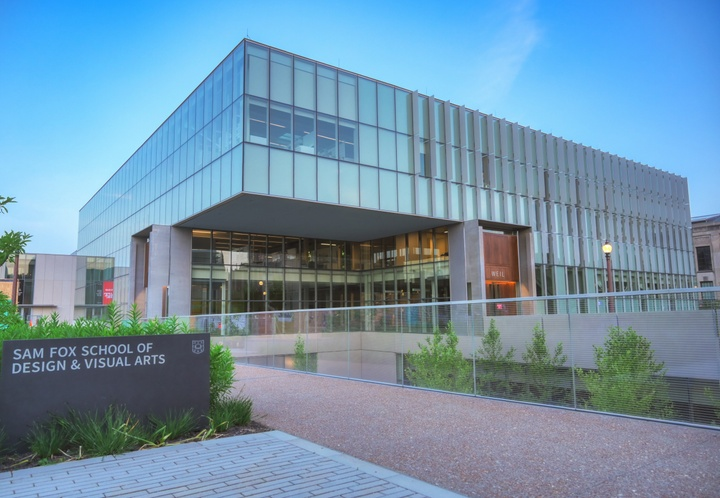 """Corner angle of Weil Hall, a three-story glass-walled building with a cantilevered corner. A granite sign in front reads """"Sam Fox School of Design & Visual Arts."""""""
