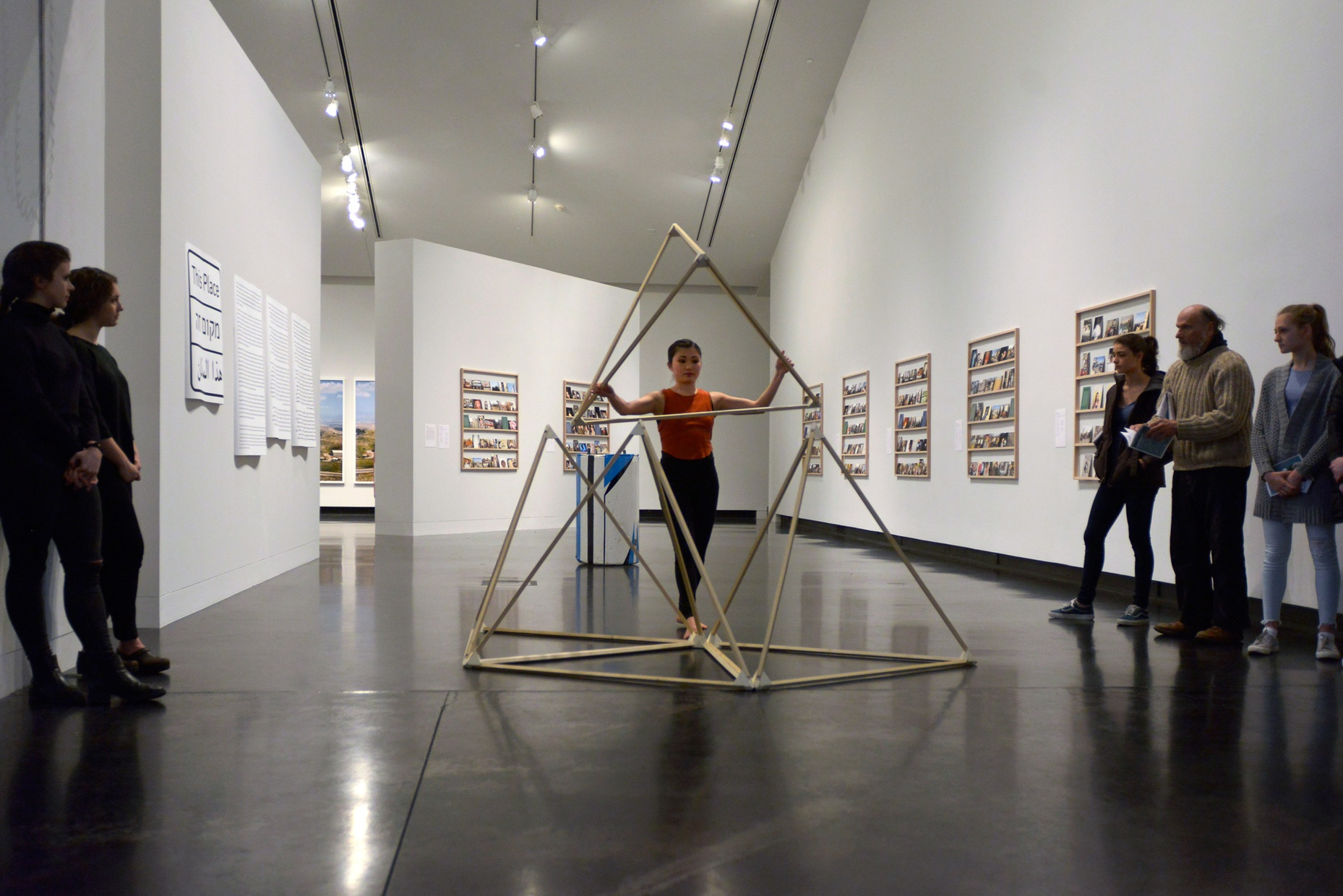 A crowd watches as a young, Asian, female dancer poses with a wooden triangular sculpture.