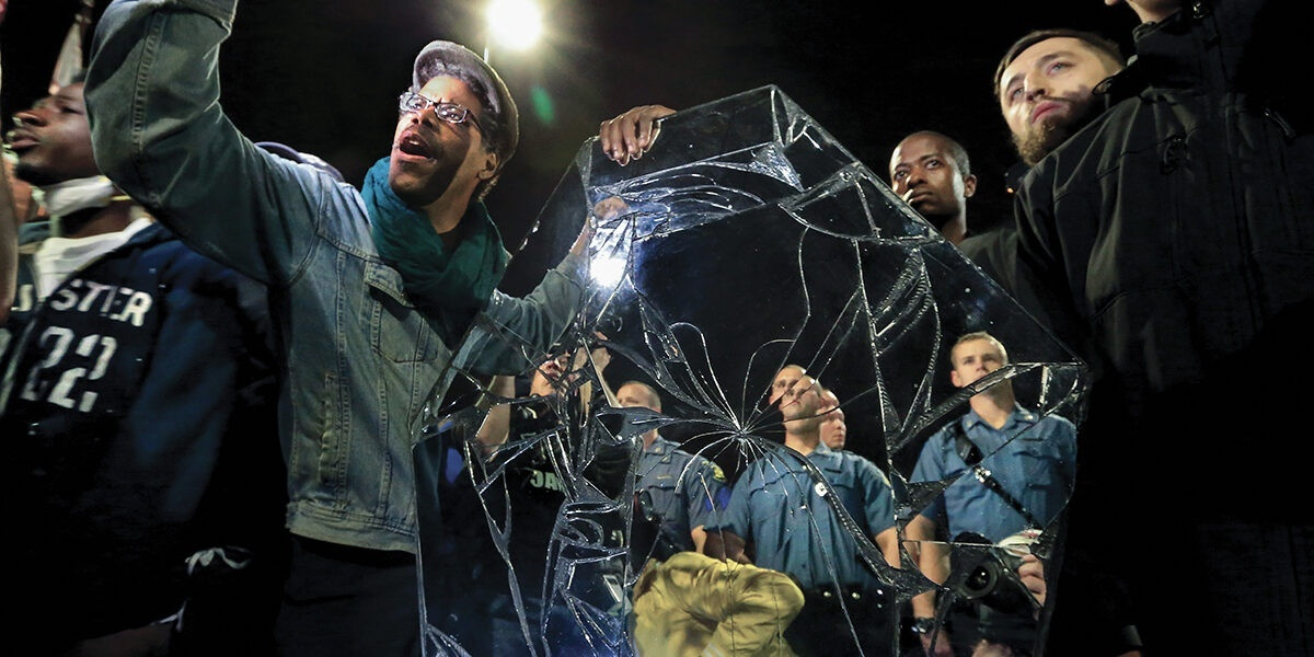 People outside at night, carrying an artwork resembling a casket covered in mirrors, with a large crack in the mirror in the foreground.