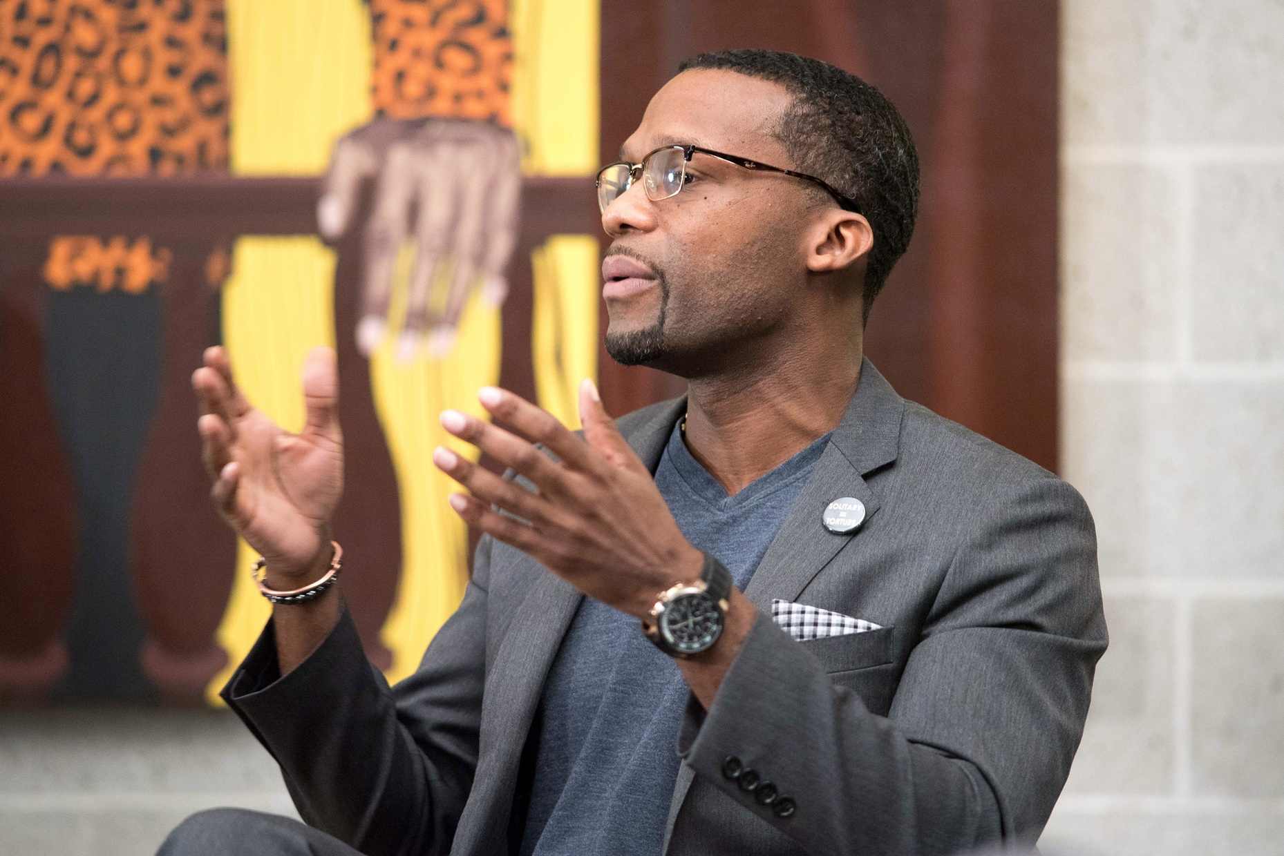 A middle-aged, black man talking with his hands raised in front of a colorful painting.