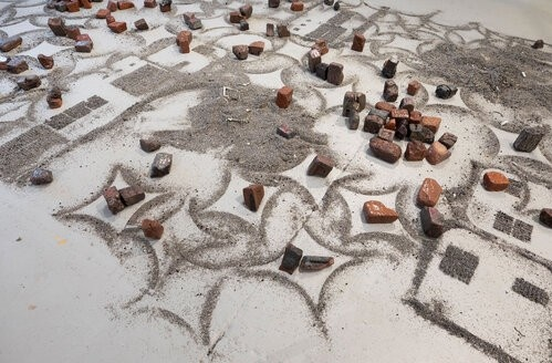 On a light grey floor, aluminum and steel fines compose themselves into straight lines, squares, curves, and four-pointed stars, emerging from formless heaps.  Melted and misshapen bricks are arranged amongst the powdered metal.