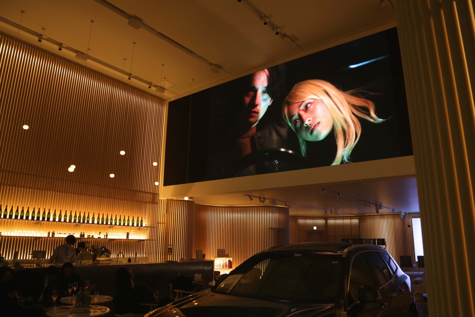 Installation view featuring a video on a wide, high screen showing two figures in the dark. Installation is set in a sleek-looking, dimly lit bar; a car is parked under the video screen next to a couple of round tables with drinks.