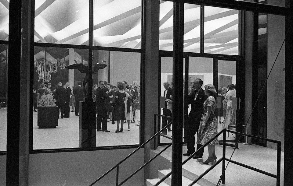 Black and white photo of the foyer of a modern-looking building with a pleated ceiling. People in fancy dress are gathered inside, one person stands in the foyer and smokes a cigarette.