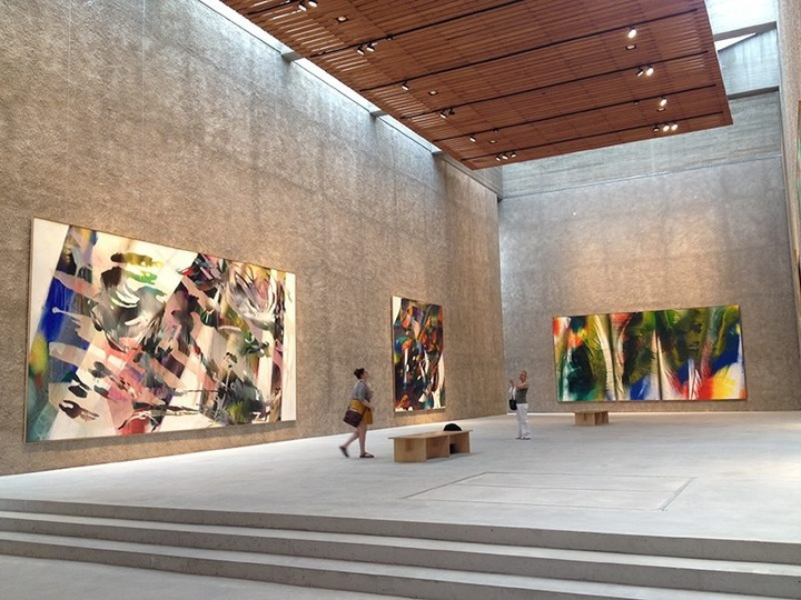 Interior of a high-ceilinged, well-lit modern gallery space with concrete walls and floor displaying large-scale abstract paintings.