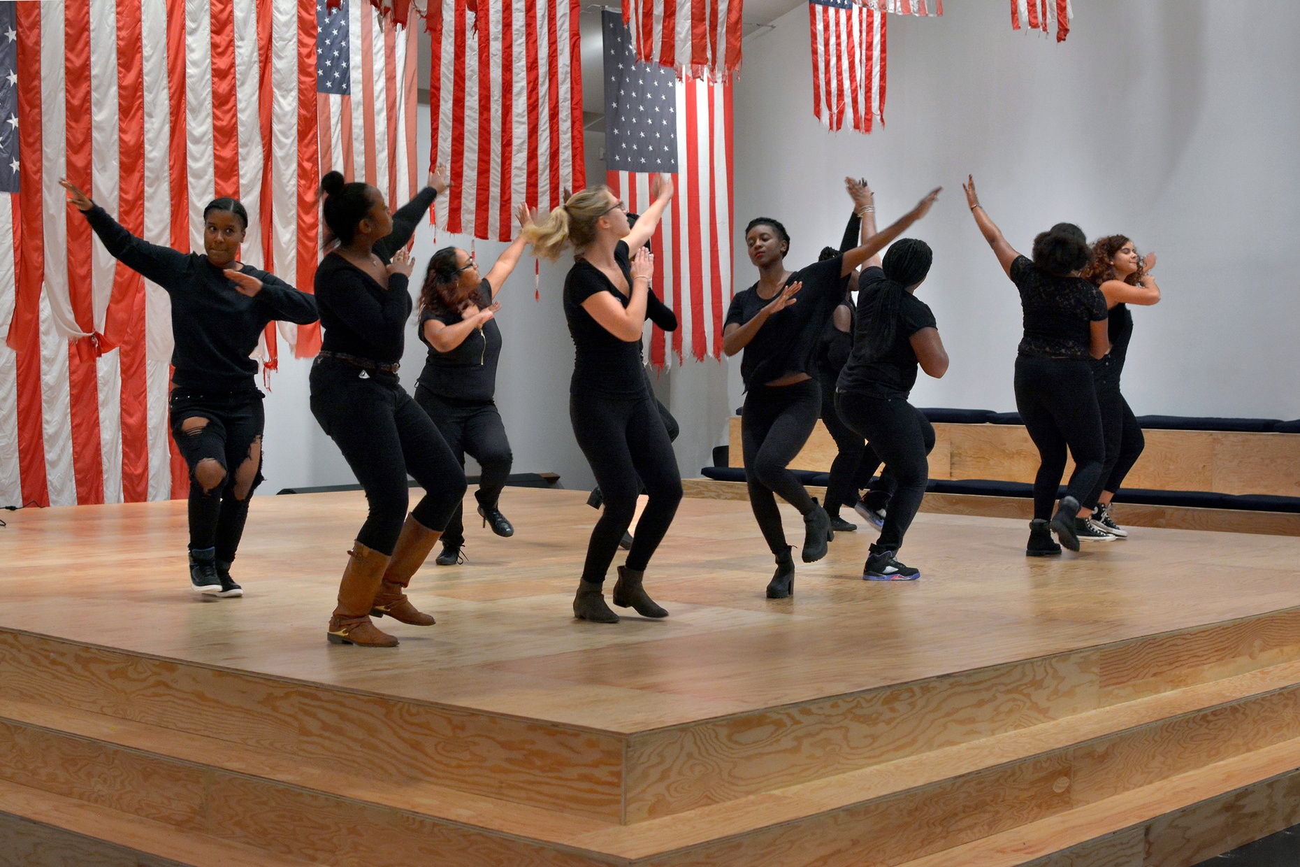 A group of people wearing black dance on a wooden stage surrounded by American flags hung from the ceiling.
