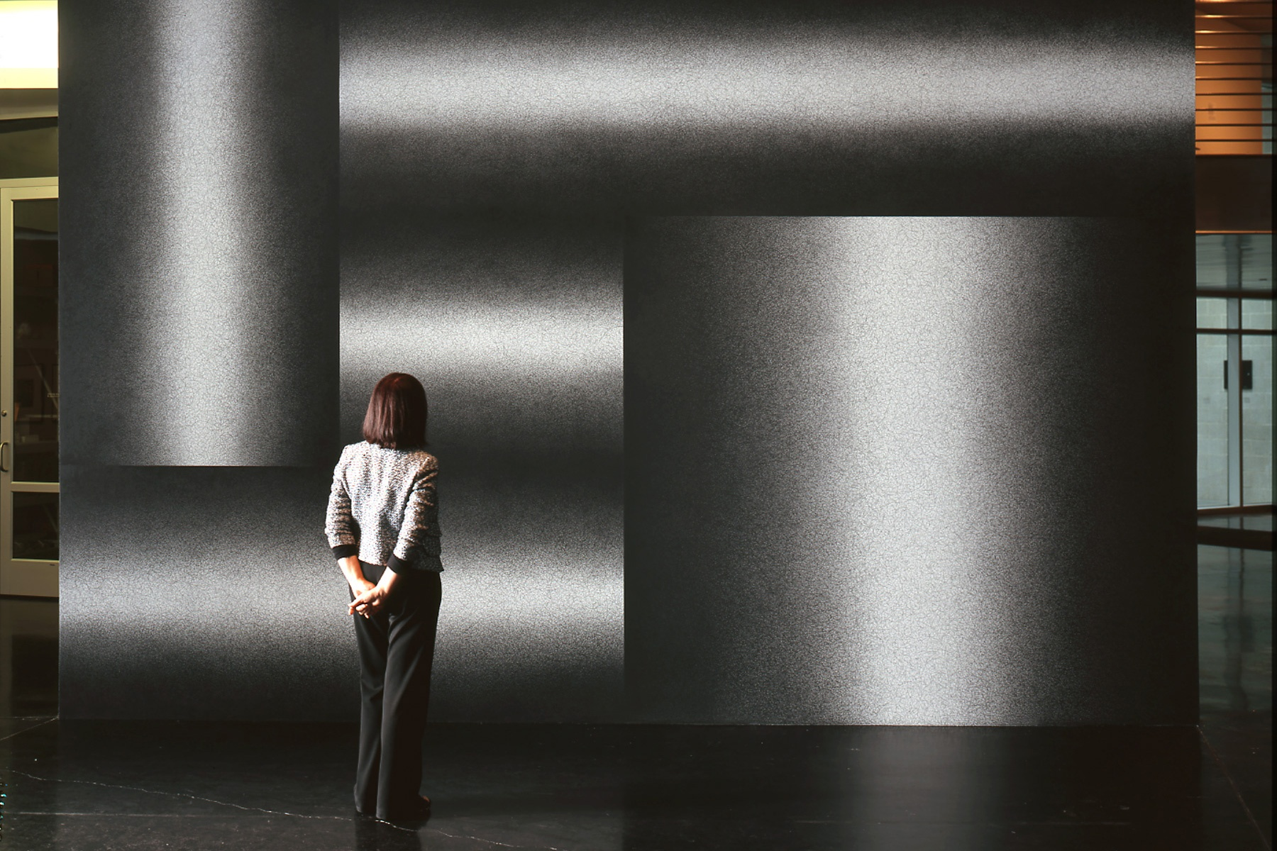 A lone female stands facing a wall decorated with multiple sections of black and white gradients.