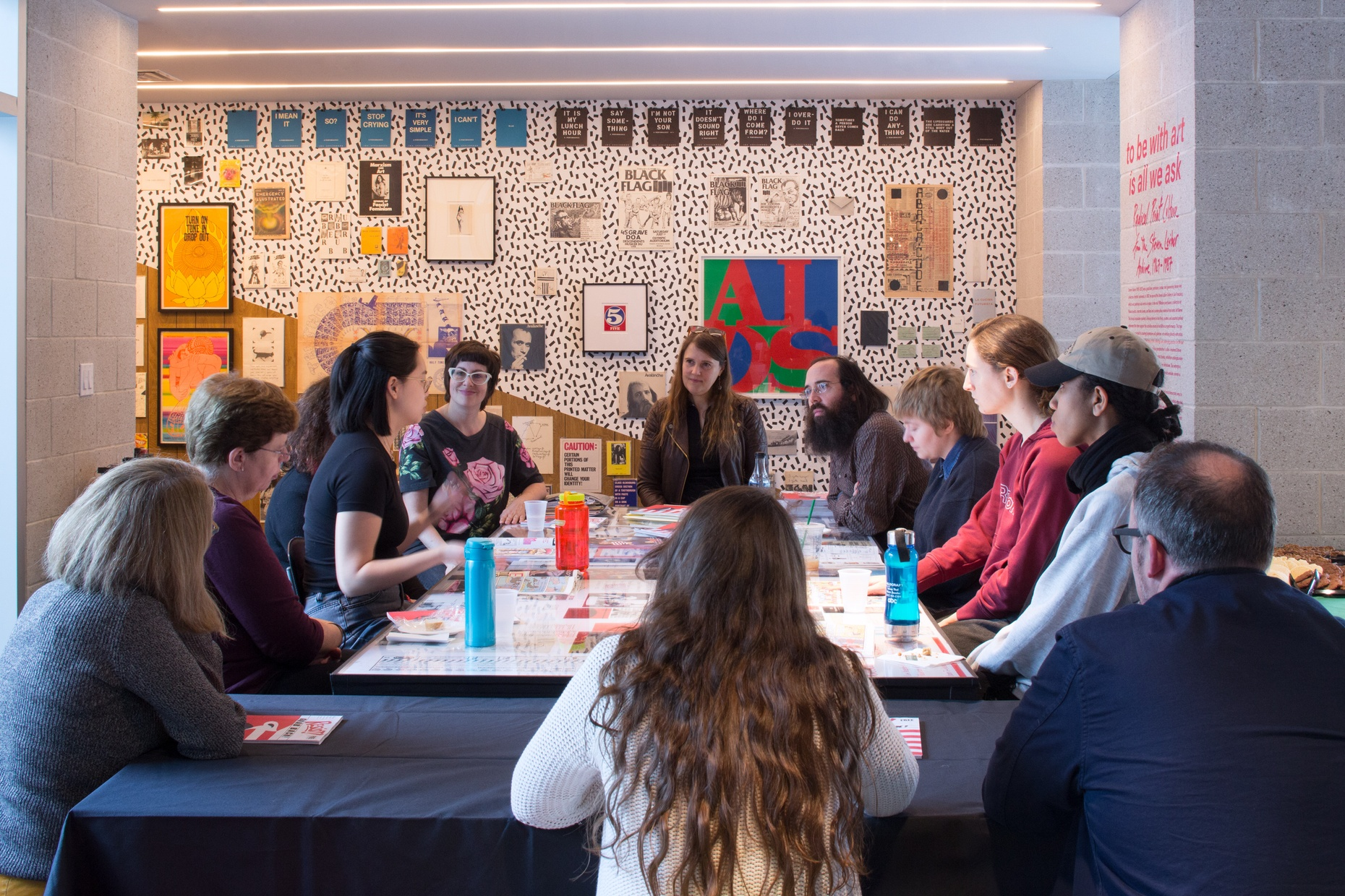 A group of people sit around a table covered with screenprints in front of a black and white polka-dot wall with colorful prints hung on it.