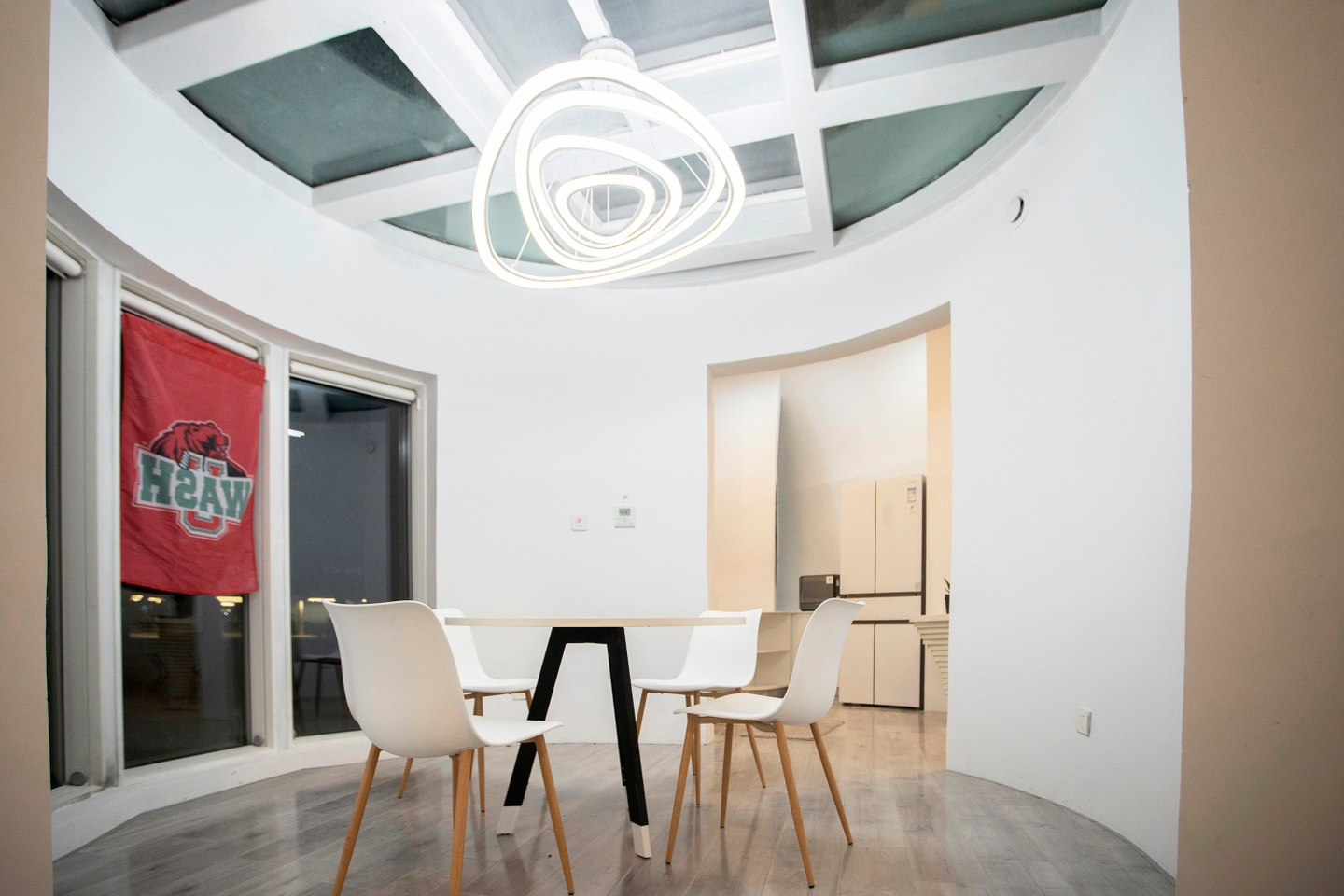Interior of the house. White walls are curved; the left side of the room features three tall windos. In the center is a table with four white chairs with wooden legs. Overhead is a bright white light composed of irregulrarly shaped rings.
