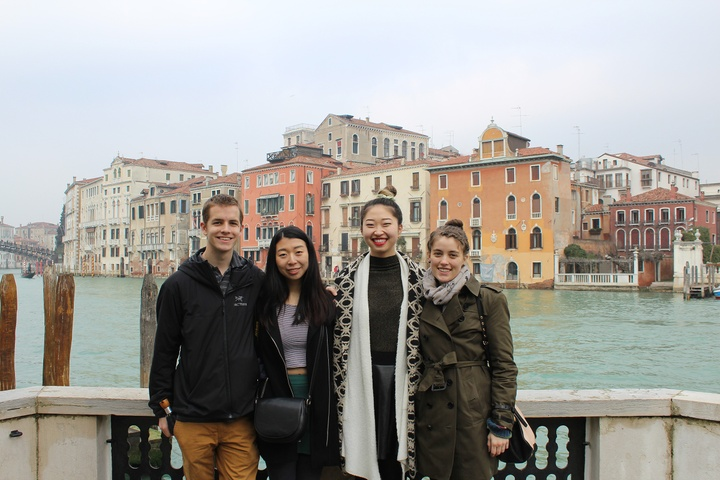 Four people in Venice standing in front of a blue canal with pink and yellow buildings behind them on a cloudy day.