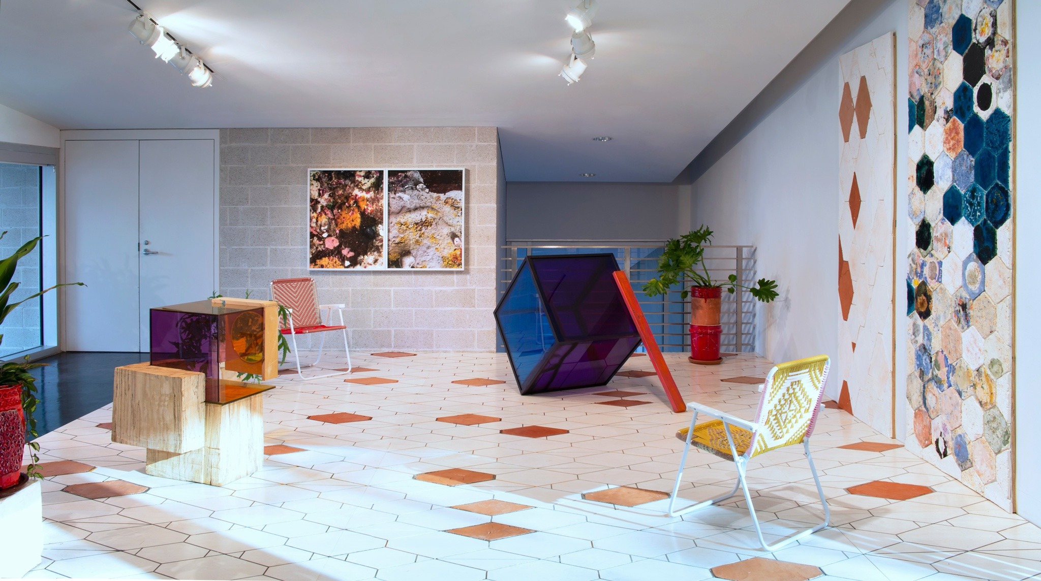 A gallery space with a tiled floor, sculptures, plants, and chairs throughout the room. Art hangs on the back wall.