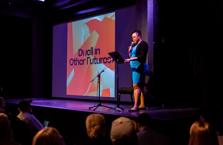 """Person on stage presents to a crowd in front of a screen reading """"Dwell in Other Futures."""""""