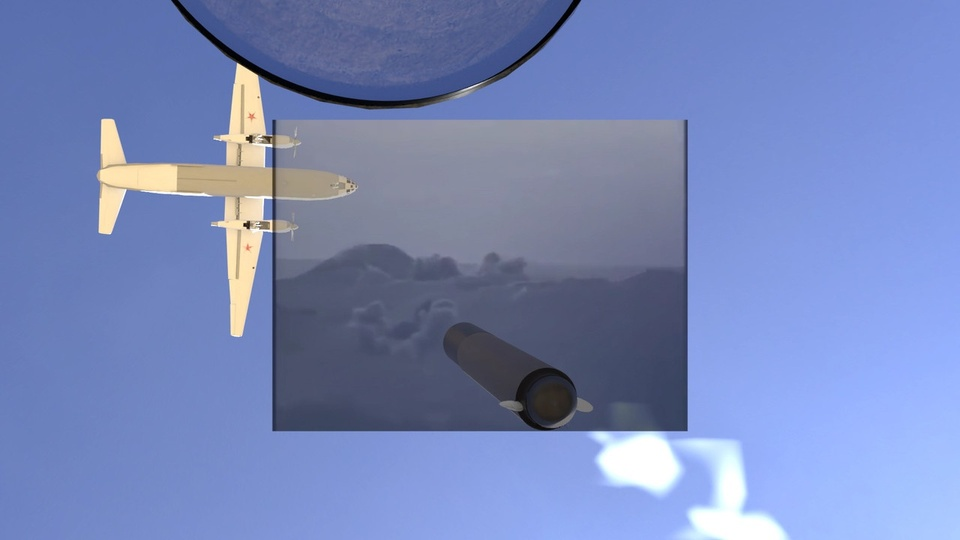Video still of a plane flying east against a blue sky, about to cross a screened rectangular box showing a cloudy sky and a missile.