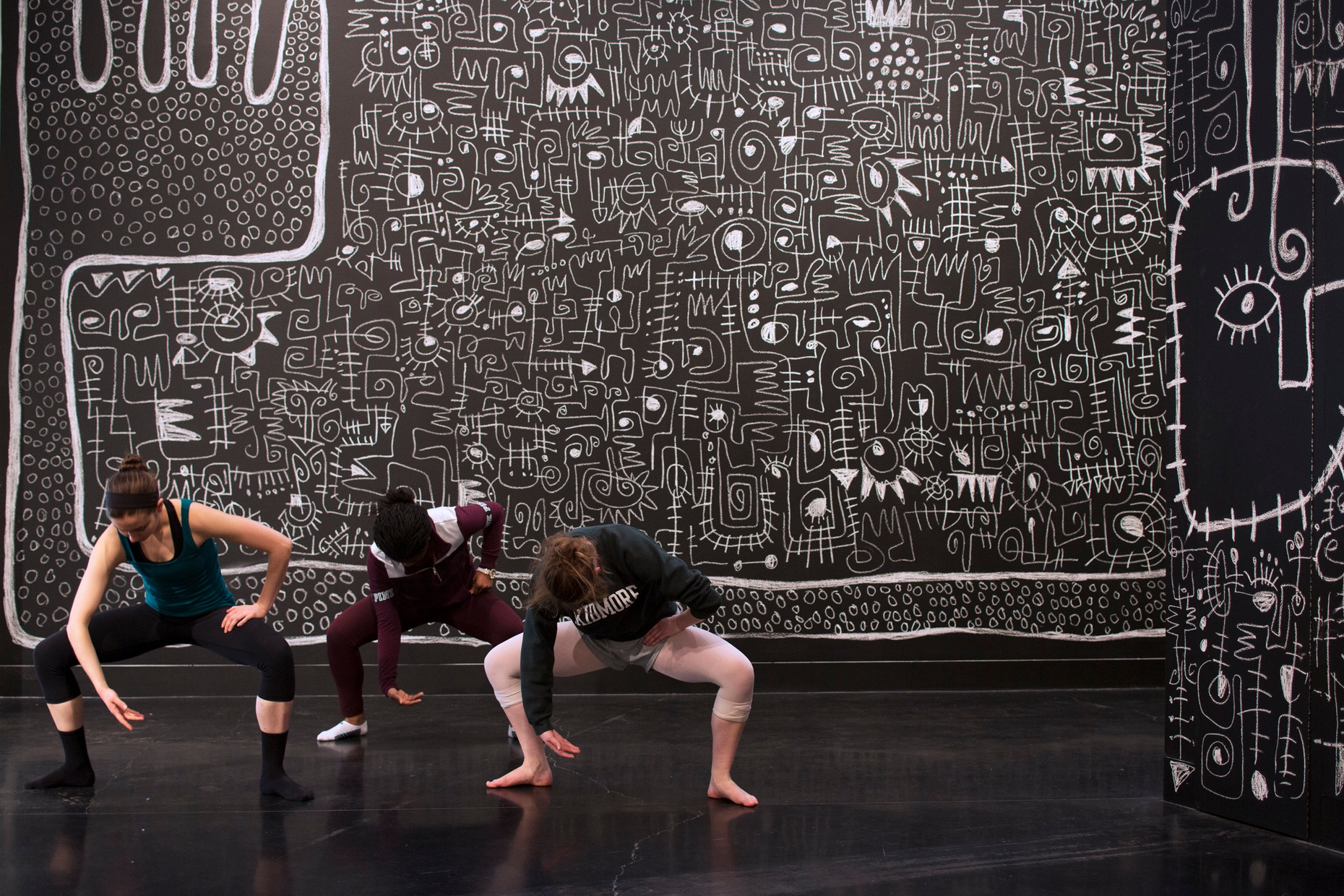 Three female dancers bend in a squat in front of a charcoal background covered in white doodles.