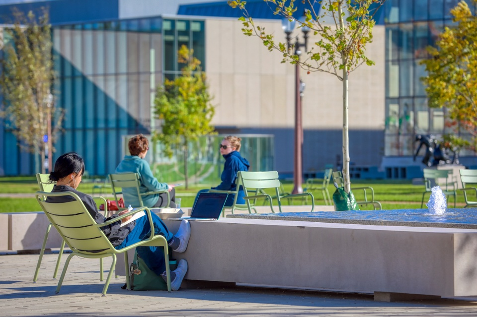 Three people relax on a brick patio with water fountains.