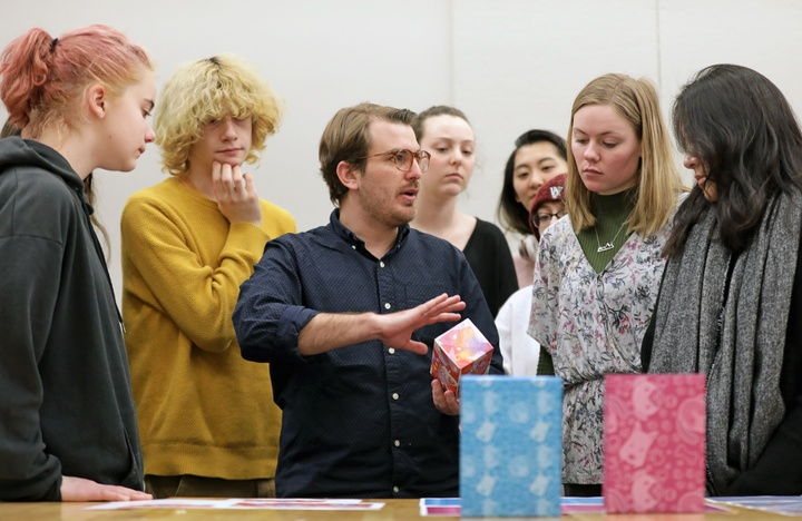 Group of people discusses samples of packaging design.