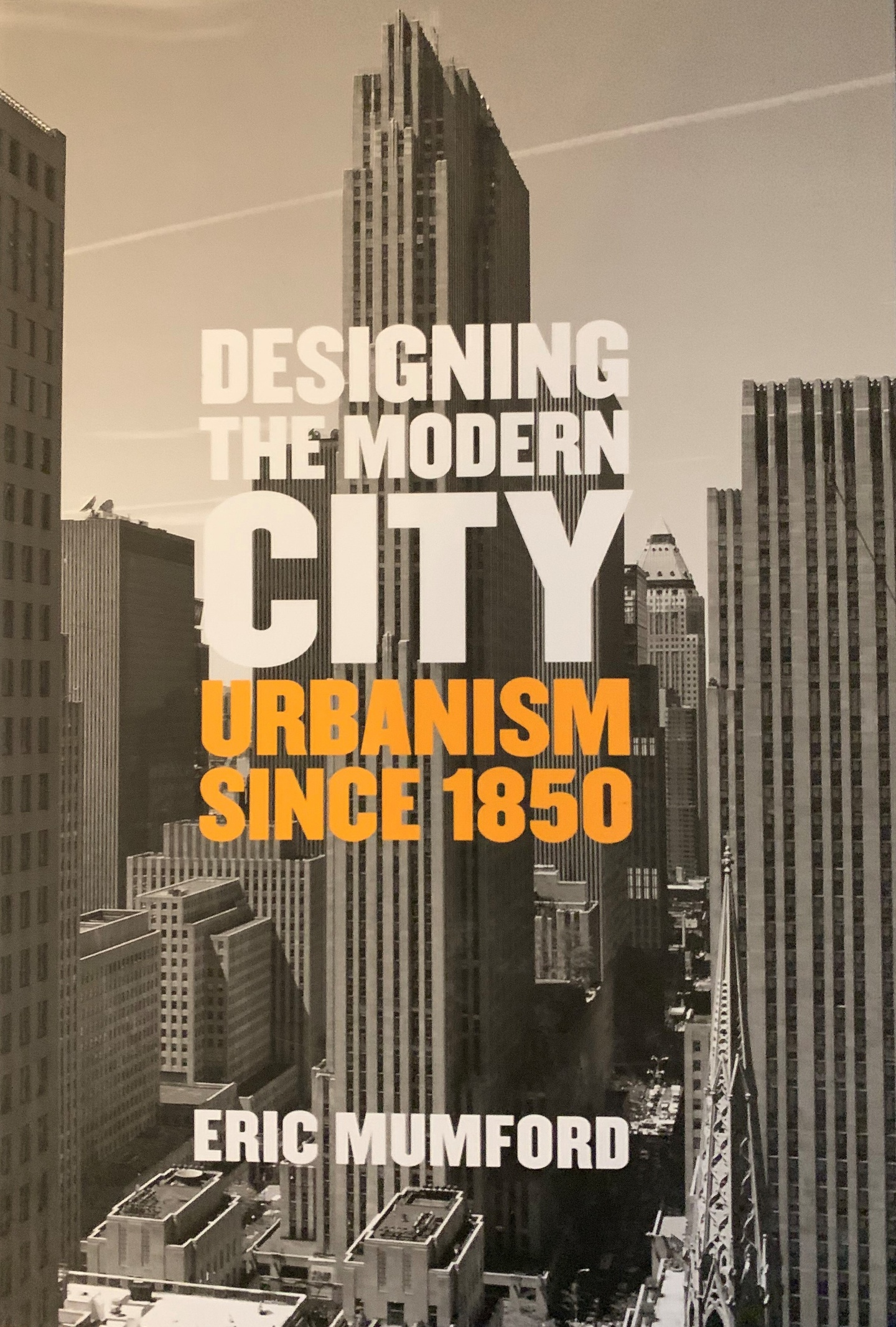 Cover of Designing the Modern City: Urbanism Since 1850, with a black-and-white photo of a cityscape with white and orange type over the top.