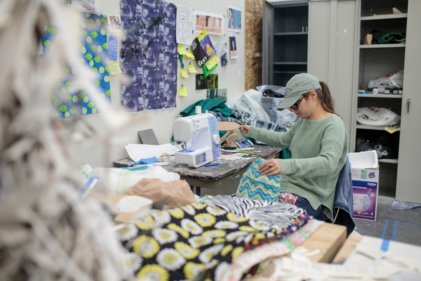 A woman sits at a sewing machine in the fashion studio. There are piles of fabric surrounding her.